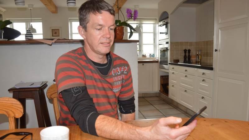 Svineproducent Jakob Krogh Andersen fra Egensøgaard i Martofte viser på sin telefon, hvordan han nu kan sidde ved køkkenbordet og have fuldt overblik over fodersituationen i samtlige siloer.