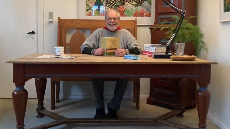Forfatter Aksel Hundslev tager i sin anden bog udgangspunkt i, hvad der gennem flere end hundrede år er sket af ofte dramatiske hændelser ved og på det gamle spisestuebord, der stod i hans fødehjem, og som nu står i hans og hans hustrus stue. Foto: Carolyn Hundslev