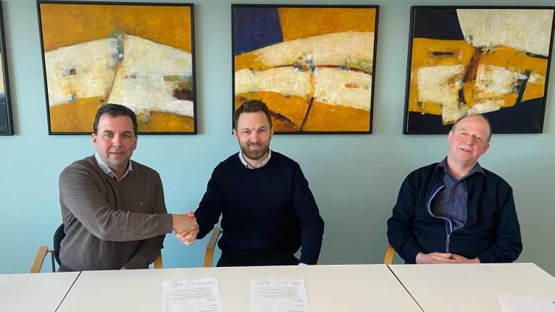 Morten Hollensen og bestyrelsesformand Peter Høj giver hånd på en underskrevet aftale. Flankeret af næstformand i Dansk Jersey Export, Niels Erik Nilsson.