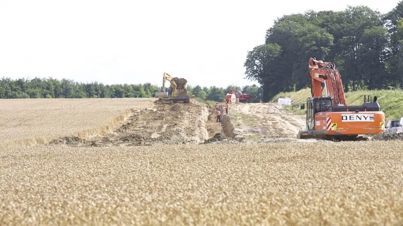 Stig Bille Brahe har regnet ud til, at maskiner med en samlet vægt på 30.000 tons har kørt i hans marker for at etablere gasledningen. Her er de tyske og belgiske entreprenører i færd med at tildække den nedgravede ledning i en hvedemark, først med harpet råjord, dernæst jord og sten og til sidst muldjorden til højre i det i alt 36 meter brede arbejdsfelt. Fotos: Erik Hansen